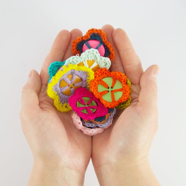 Knopfblumen in der Hand