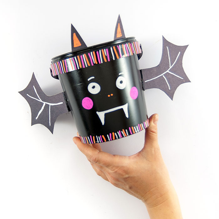 """Mit meinem super einfachen DIY-Halloween-Süßigkeiten-Eimer läuft die """"Süßes-oder-Saures-Runde"""" der Kids dieses Jahr hoffentlich möglichst kontaktlos ab. Der Eimer ist schnell aus einem upcycelten Joghurtbecher gebastelt – das macht bestimmt auch den Kids Spaß!"""